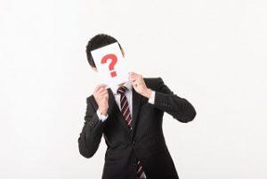 ?で顔を隠すスーツ男性