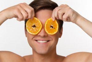 スライスしたオレンジをもつ外国人男性